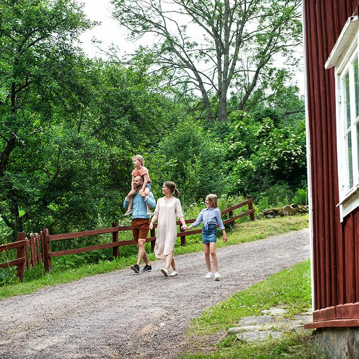 Familj går på grusväg i Småland